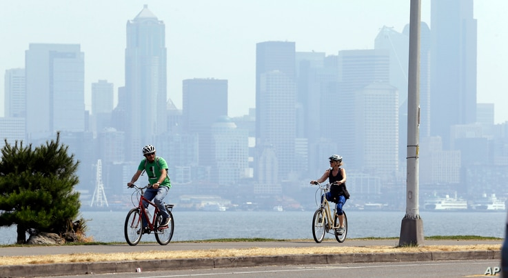 FILE - Cyclists pedal in view of downtown Seattle, cloaked in a haze of smoke from fires raging in British Columbia that swept down into the Puget Sound region, Aug. 3, 2017. Seattle, like many cities in the Northwest, has been plagued by hazardous s...