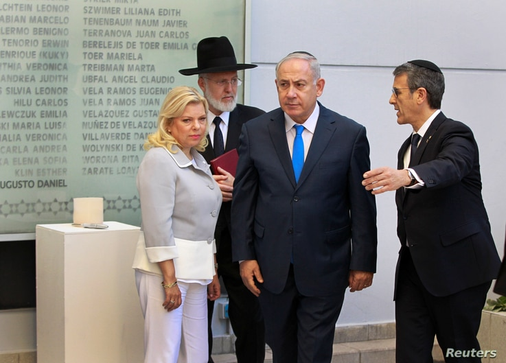 Israeli Prime Minister Benjamin Netanyahu, from left, and his wife Sara, alongside Agustin Zba, President of the Argentine Israeli Mutual Association Jewish community center, walk past a wall with names of the victims of the 1994 AMIA bombing in Buen...
