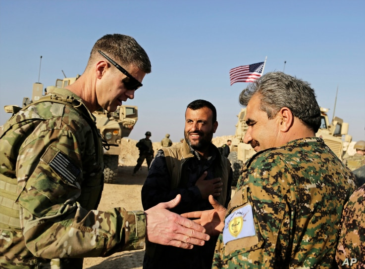 U.S. Army Maj. Gen. Jamie Jarrard left, thanks Manbij Military Council commander Muhammed Abu Adeel during a visit to a small outpost near the town of Manbij, northern Syria, Feb. 7, 2018.