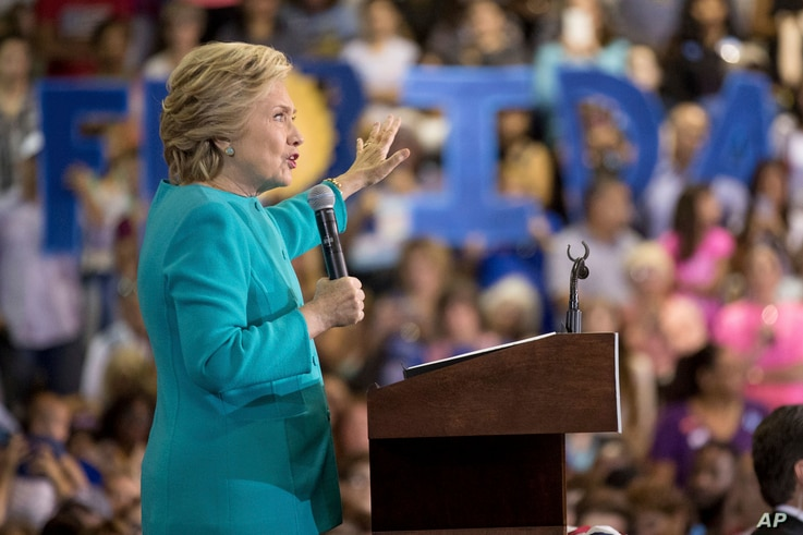 """Members of the audience hold signs that spell out """"Florida"""" as Democratic presidential candidate Hillary Clinton speaks at a rally at Palm Beach State College in Lake Worth, Florida, Oct. 26, 2016."""