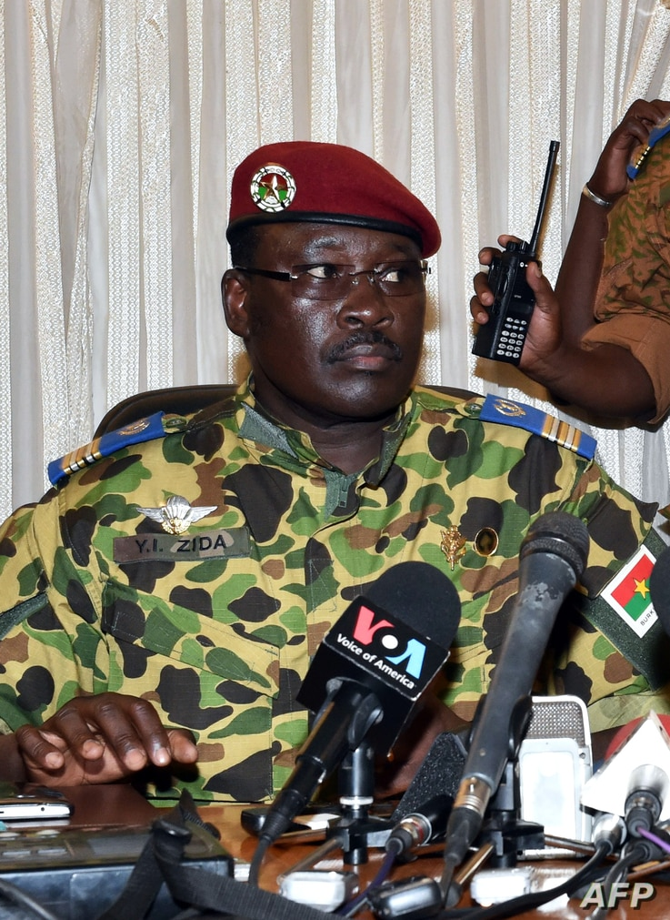 Burkina Faso's Lieutenant-Colonel Yacouba Isaac Zida (L) listens a statement is read at the end of a meeting with the country's military commanders,  Nov. 1, 2014, at the military headquarters in Ouagadougou.