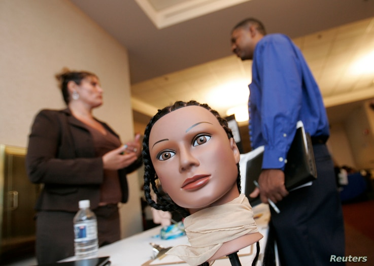 FILE - A potential applicant talks to Michelle Leonard, owner of Pittsburgh Multicultural Cosmetology Academy, at a job fair in Pittsburgh, Pa.