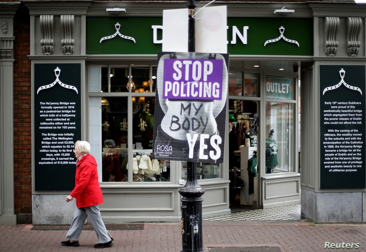 A woman walks past a pro-choice poster in the city centre of Dublin, Ireland, May 22, 2018.
