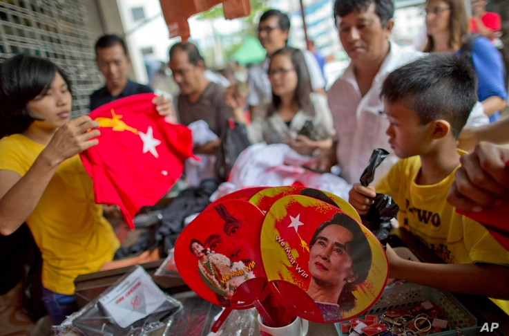 People gather to buy merchandise with pictures of Myanmar opposition leader Aung San Suu Kyi at a shop run by her National League of Democracy party in Yangon, Myanmar, Nov. 10, 2015. Her party accused the government of delaying eleciton results.