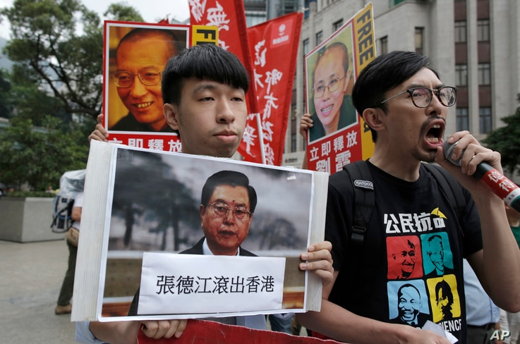 Pro-democracy activists carry pictures of the visiting Chairman of the Standing Committee of China's National People's Congress, Zhang Dejiang, along with detained Chinese Nobel Peace laureate Liu Xiaob and his wife Liu Xia, as they march to the Gove...