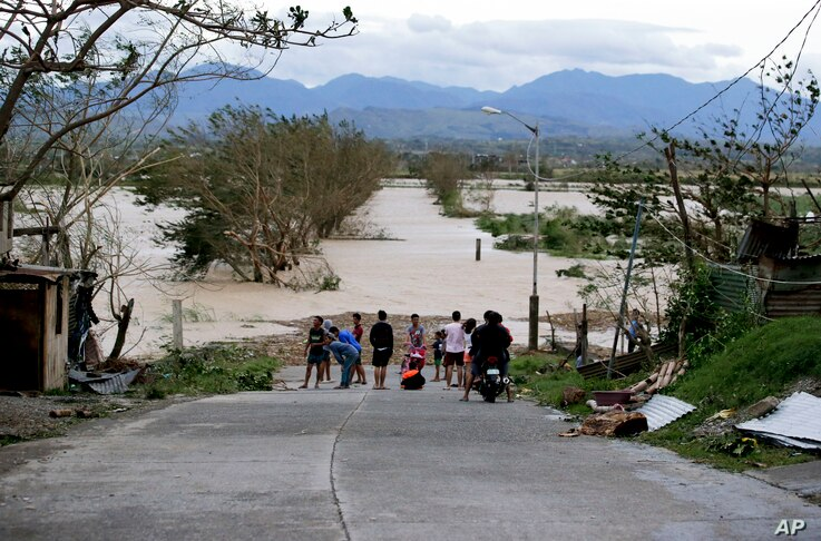 Residents stand by a flooded road following the onslaught of Typhoon Mangkhut in Tuguegarao city in Cagayan province, northeastern Philippines, Sept. 15, 2018.