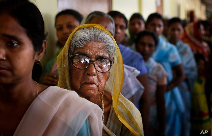 An elderly woman watches as she stands in a line to cast her vote during the first phase of elections in Dibrugarh, in the northeastern state of Assam, India, April 7, 2014.