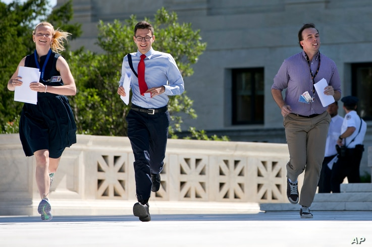 FILE - Interns run with a decision across the plaza of the Supreme Court in Washington, June 29, 2015.