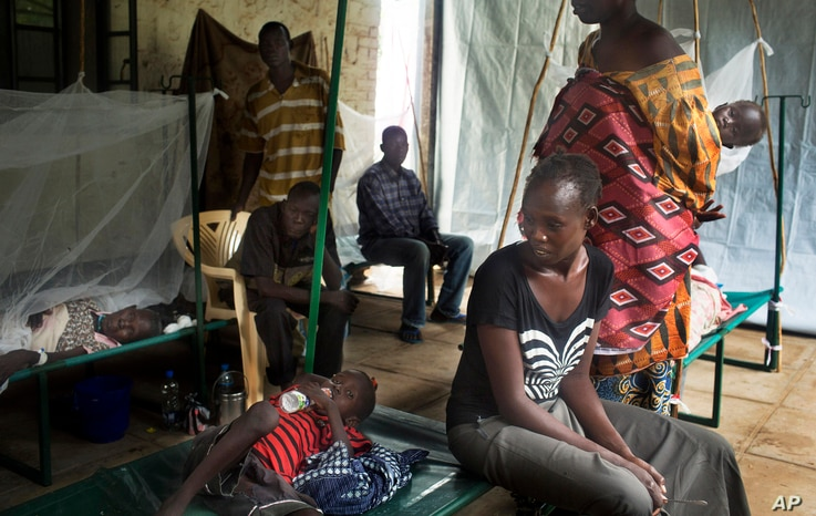 FILE - In this May 24, 2014 file photo a South-Sudanese family waits in the cholera isolation ward of Juba Teaching Hospital in the capital Juba.