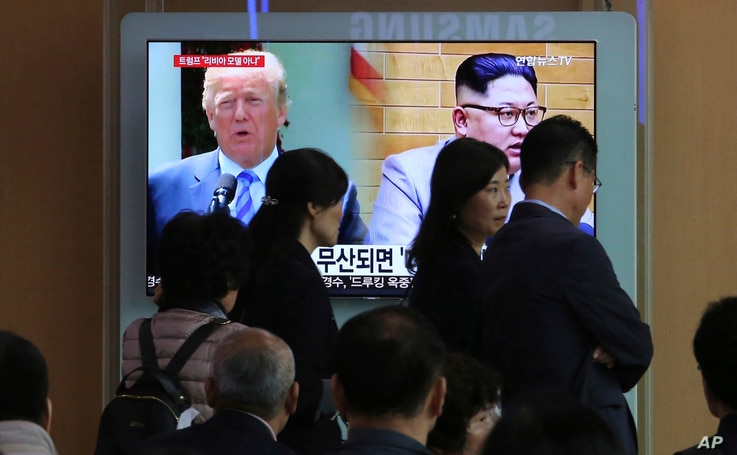 People pass by a TV screen showing file footage of U.S. President Donald Trump, left, and North Korean leader Kim Jong Un during a news program at the Seoul Railway Station in Seoul, South Korea, May 18, 2018.