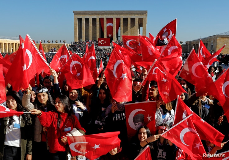 People wave Turkish flags as they attend the Republic Day ceremony at Anitkabir, the mausoleum of modern Turkey's founder Ataturk, to mark the republic's anniversary in Ankara, Turkey, Oct. 29, 2018.