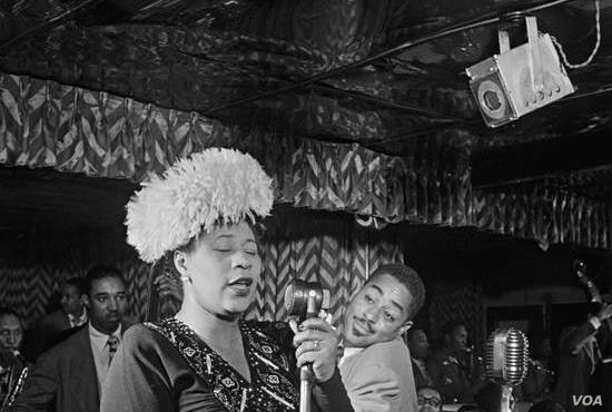 Ella Fitzgerald sings at the Downbeat Club in New York, with Dizzy Gillespie in the background, 1947. (William Gottlieb/Library of Congress)Ella Fitzgerald sings at the Downbeat Club in New York, with Dizzy Gillespie in the background, 1947. (William...