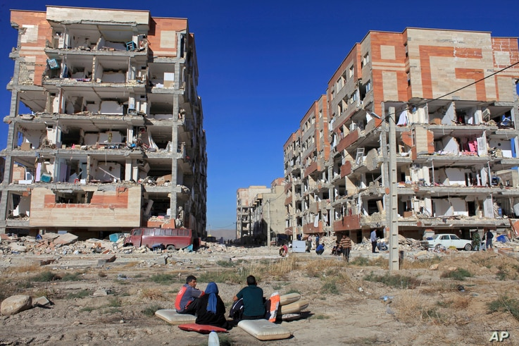 Survivors sit in front of buildings damaged by an earthquake, in Sarpol-e-Zahab, western Iran, Nov. 13, 2017.