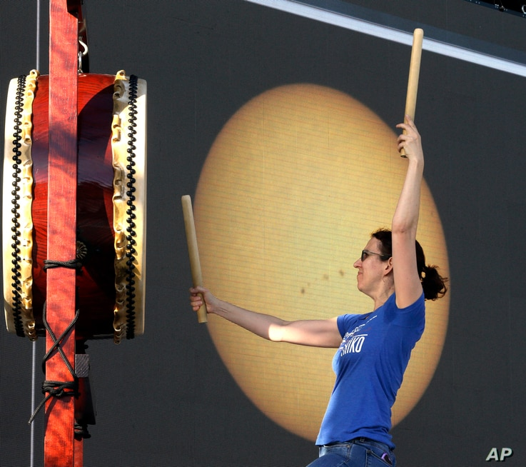 A large screen with a live telescope feed of the sun is visible behind Karen Tingey as she drums with Portland Taiko during a rehearsal in preparation for Monday's solar eclipse, in Salem, Ore.