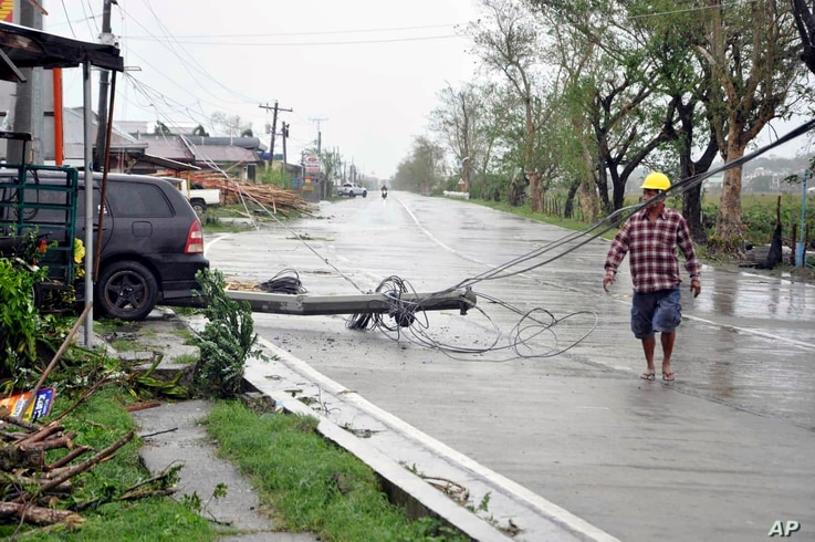 A resident walks on the highway amidst a toppled electric post after Typhoon Yutu slammed Isabela province in northeastern Philippines, Oct. 30, 2018.