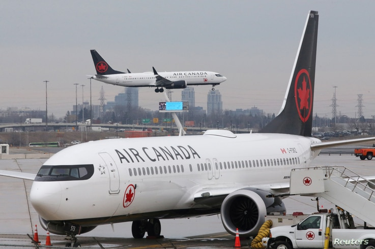An Air Canada Boeing 737 MAX 8 from San Francisco approaches for landing at Toronto Pearson International Airport over a parked Air Canada Boeing 737 MAX 8 aircraft in Toronto, Ontario, Canada, March 13, 2019.
