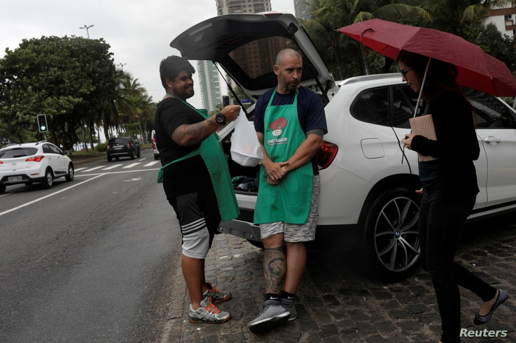 Stefan Weiss (L) and Alexander Costa sell food out of the trunk of a car in Rio de Janeiro, Brazil, Sept. 17, 2018.