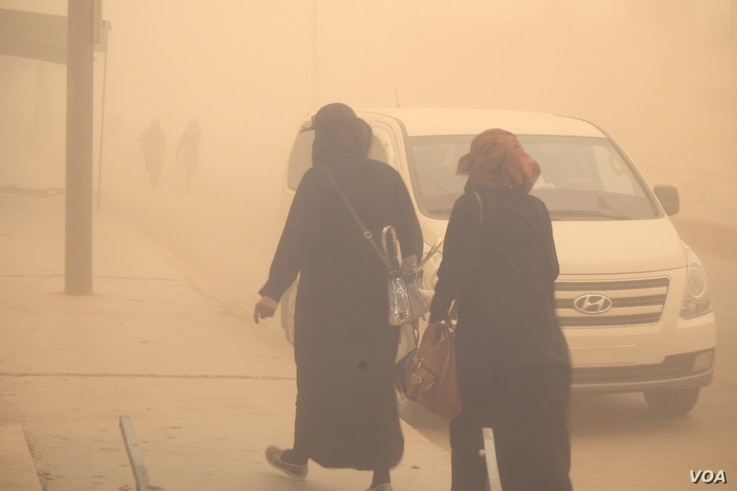 Families hurry indoors as the sandstorm begins, saying although the current local leadership provides security, they are still without electricity and hospitals, in al-Shadady, Syria, Oct. 28, 2017. (H. Murdock/VOA)