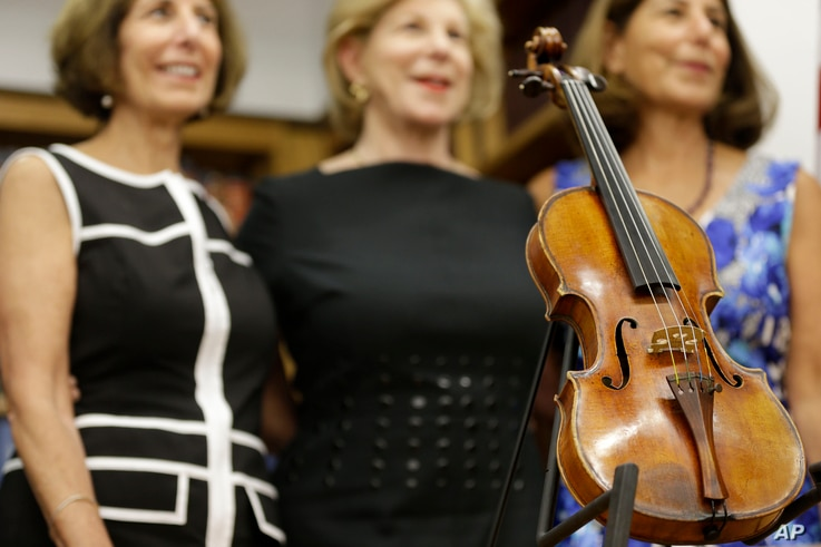 Sisters Jill Totenberg, left, Nina Totenberg, center, and Amy Totenberg pose for pictures with the recovered Ames Stradivarius violin during a news conference in New York, Aug. 6, 2015.