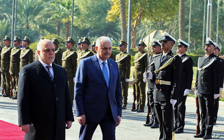 Iraq's Prime Minister Haider al-Abadi, left, and Turkish Prime Minister Binali Yildirim inspect an honor guard during a welcome ceremony in Baghdad, Iraq, Jan. 7, 2017.