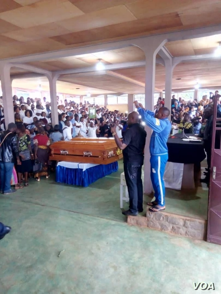 Mourners gather for Nancy Azah and her husband, Njong Padisco, both nurses killed in Cameroon's northwest region, during their funeral services in Alahkuma, Aug. 15, 2018.