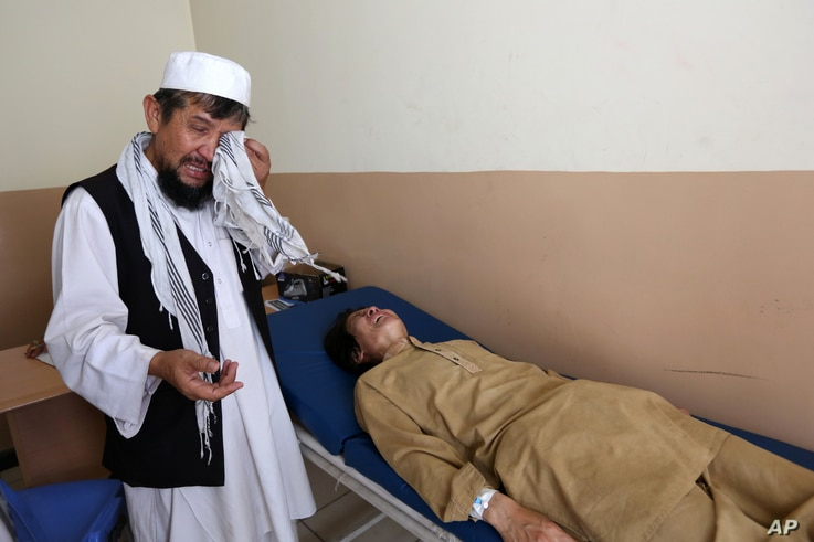 FILE -  An Afghan patient is seen on the bed as a father weeps in the Mental Health and Drug Addicts' Hospital in Kabul, Afghanistan. After almost 40 years of conflict and crisis, experts say the vast majority of the Afghan population suffers from so...