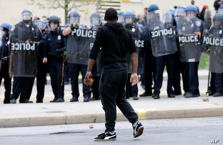 A demonstrator walks past police with a brick as they respond to thrown objects, after the funeral of Freddie Gray in Baltimore, April 27, 2015.