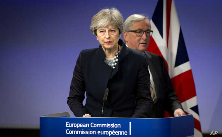 European Commission President Jean-Claude Juncker, right, walks behind British Prime Minister Theresa May prior to addressing a media conference at EU headquarters in Brussels, Dec. 4, 2017.