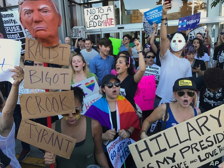 Protesters hold banners during a rally outside the CNN studio in opposition to President-elect Donald Trump, in the Hollywood section of Los Angeles, Nov. 13, 2016.