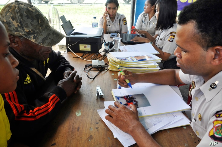 Relatives of passengers on the missing Trigana Air Service flight listen to a National Policies Disaster Victim Identification official at Sentani airport in Jayapura, Papua province, Indonesia, Aug. 17, 2015.