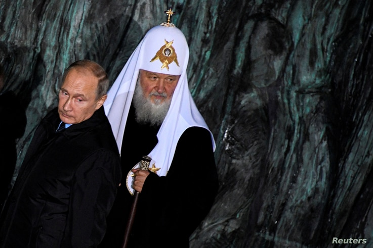 """FILE - Russian President Vladimir Putin and Patriarch Kirill, the head of the Russian Orthodox Church, attend a ceremony unveiling the country's first national memorial to victims of Soviet-era political repressions called """"The Wall of Grief"""" in Mosc..."""