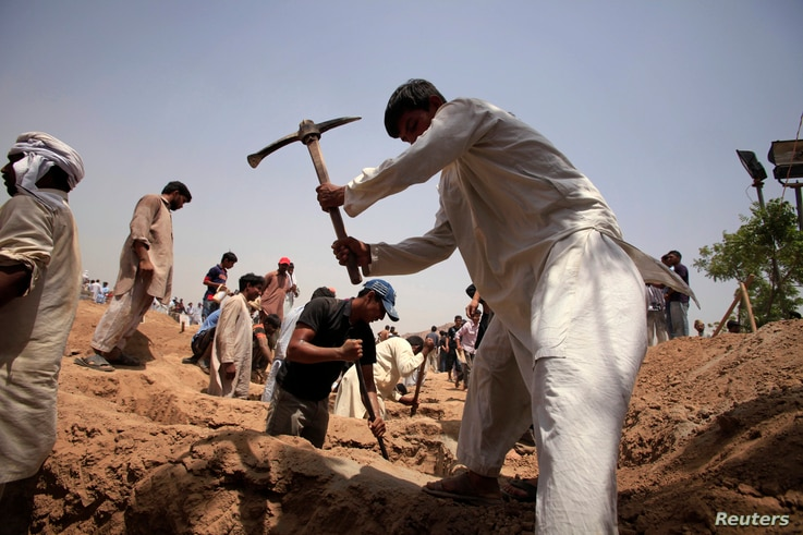 FILE - Members of the Ahmadi Muslim community dig graves for victims in Chenab Nagar, located in Punjab's Chiniot District, about 200 km (124 miles) northwest of Lahore. At least 70 people were killed in the attack.