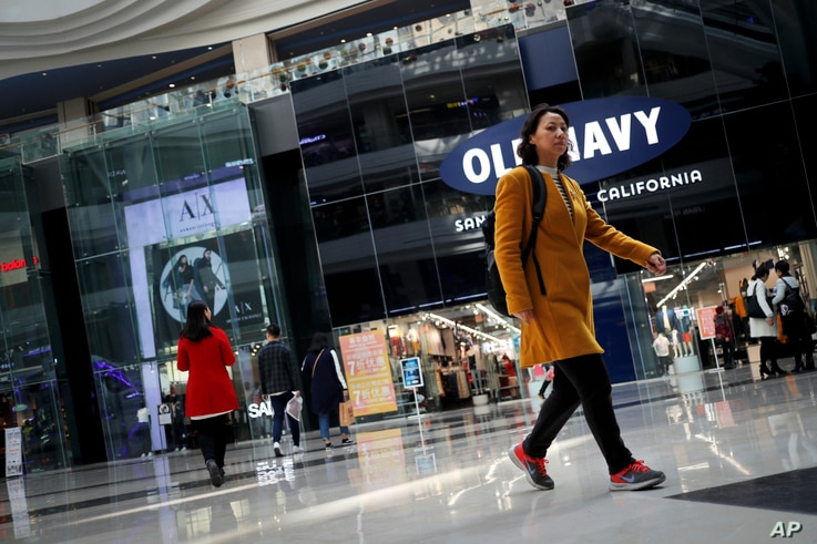 people walk near foreign brands fashion outlets at a shopping mall in Beijing, China, March 2, 2017.