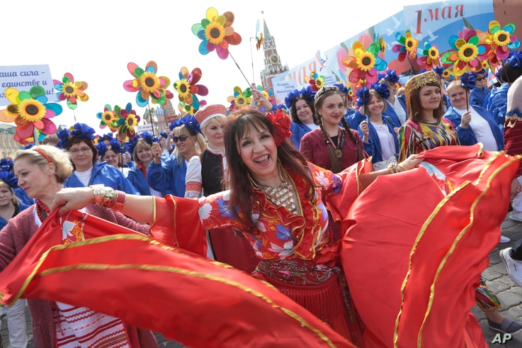Russians dance as they parade on Red Square to mark May Day in Moscow, May 1, 2017, with the Spassky Kremlin tower in the background.
