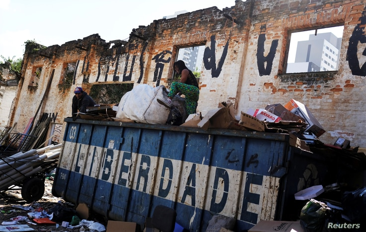 """Fabiana Silva sells her collected wares to a cardboard recycler in Moinho favela, in Sao Paulo, Brazil, July 6, 2017. The word on the container is """"Freedom."""""""