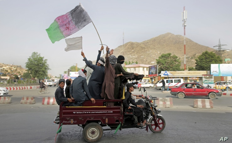 FILE - Taliban fighters and their supporters carry a representation of the Afghan national flag and a Taliban flag while riding in a motorized vehicle, in Kabul, Afghanistan, June 17, 2018.
