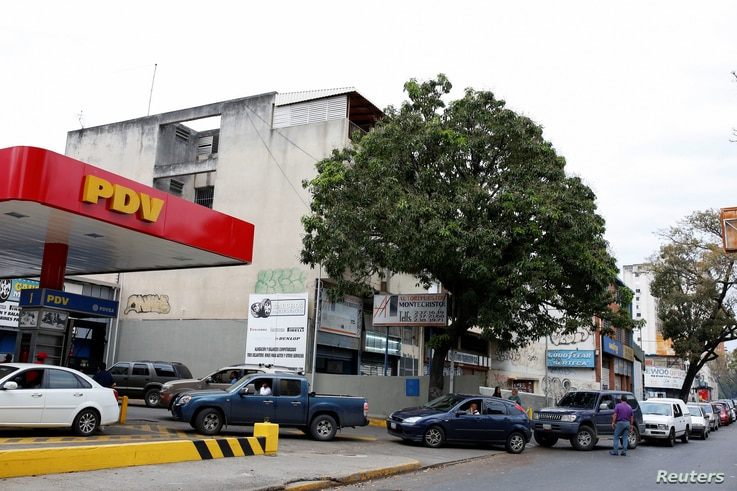 People wait in line to fill the tanks of their cars at a gas station of the state oil company PDVSA in Caracas, Venezuela, March 22, 2017.