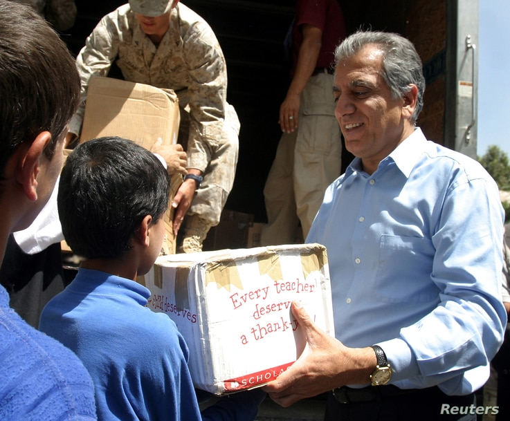 FILE - Zalmai Khalilzad, U.S.'s special envoy and ambassador to Afghanistan (R) hands out parcels of toys sent by U.S. people to an orphanage in Kabul, providing meals and schooling for street children, August 8, 2004.