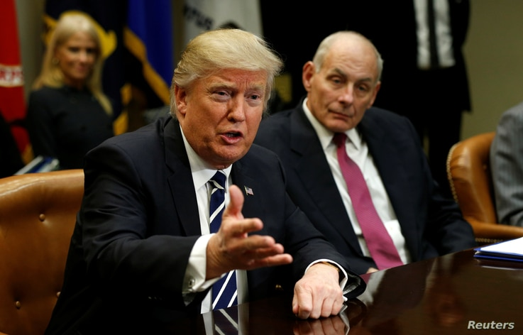 Homeland Security Secretary John Kelly, right, listens to U.S. President Donald Trump during a meeting with cybersecurity experts in the Roosevelt Room of the White House in Washington, Jan. 31, 2017.