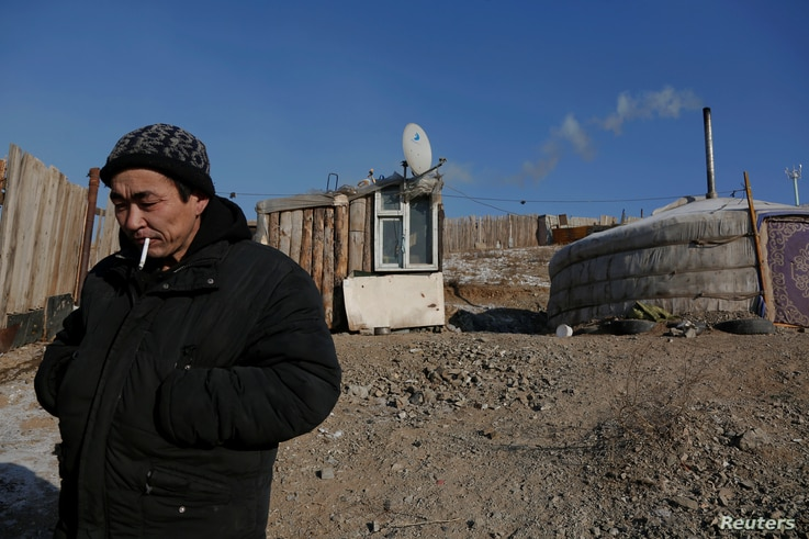 Setevdorj Myagmartsogt smokes a cigarette outside his tent-like ger home, which is heated by coal burning stove, in Ulaanbaatar, Mongolia, Jan. 29, 2017.