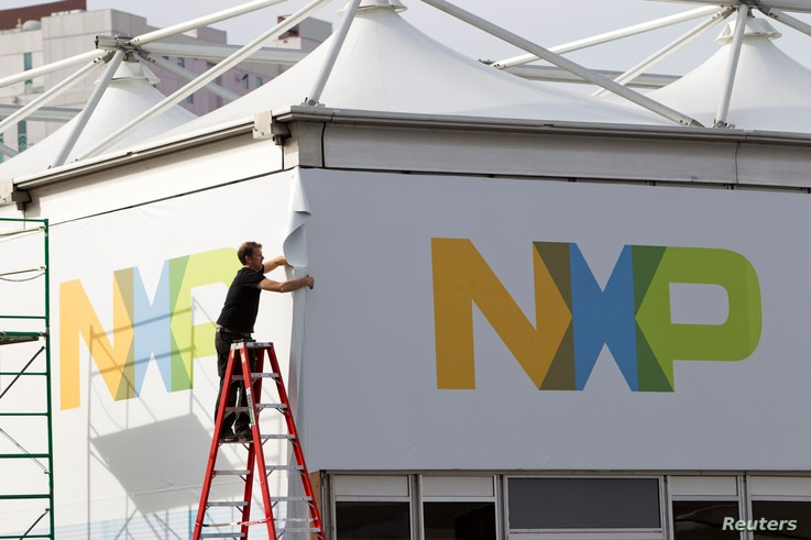 FILE - A man works on a tent for NXP Semiconductors in preparation for the 2015 International Consumer Electronics Show (CES) at Las Vegas Convention Center in Las Vegas, Nevada, Jan. 4, 2015.
