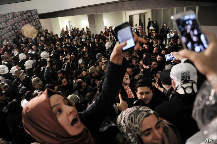 FILE - Journalists react as riot police enter the headquarters of Turkey's largest-circulation newspaper Zaman in Istanbul, March 4, 2016.