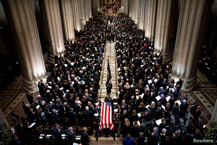 The Honor Guard carries the casket of former president George Herbert Walker Bush down the center isle following a memorial ceremony at the National Cathedral in Washington, Dec. 5, 2018.