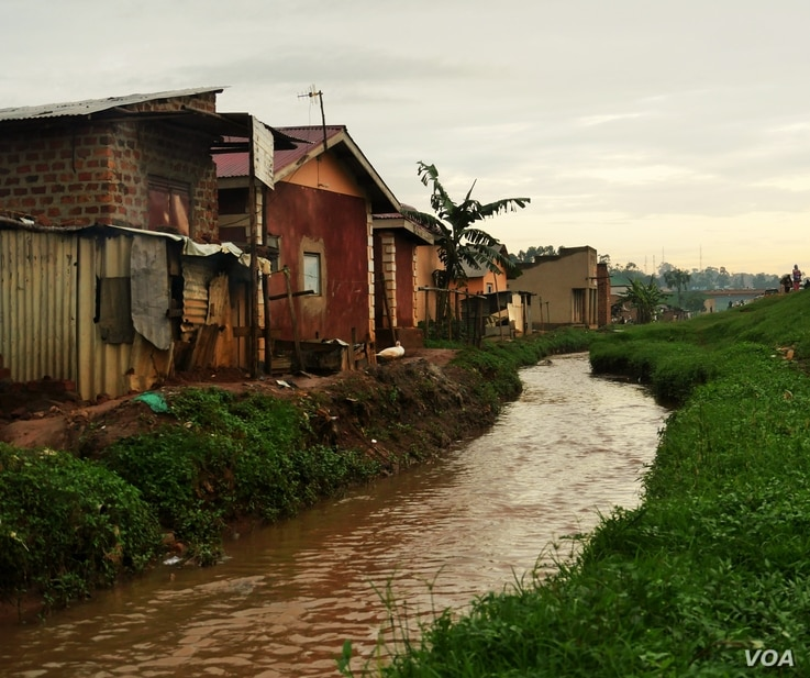 Although drainage channels have been built, homes are often built right up to the edge. Waste dumped in such channels often leads to flooding in low lying homes. (E. Paulat/VOA)