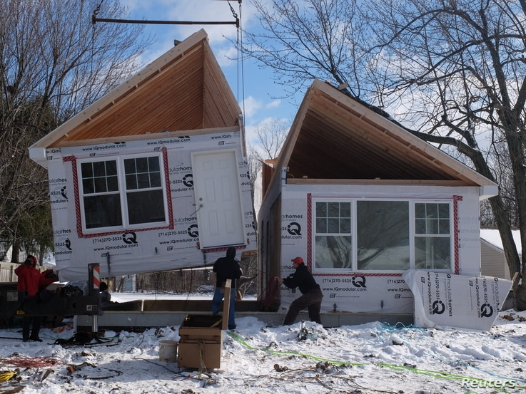 Workers prepare to put together a single-family modular home in Depew, New York, in Feb. 2017.