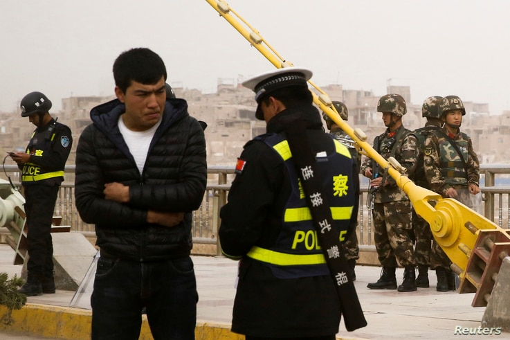 A police officer checks the identity card of a man as security forces keep watch in a street in Kashgar, Xinjiang Uighur Autonomous Region, China, March 24, 2017.