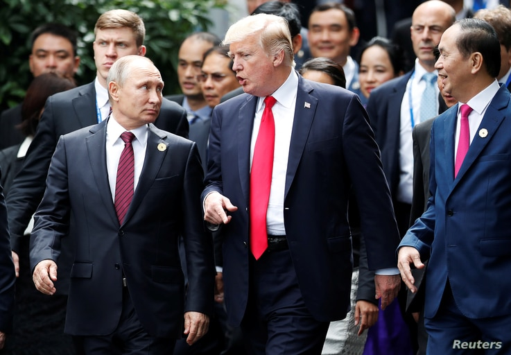 U.S. President Donald Trump and Russia's President Vladimir Putin talk as Vietnam's President Tran Dai Quang, right, looks on, during the photo session at the APEC Summit in Danang, Vietnam, Nov. 11, 2017.