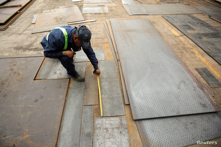 FILE - An employee measures steel plates at Kalisch Steel factory in Ciudad Juarez, Mexico, March 27, 2018.