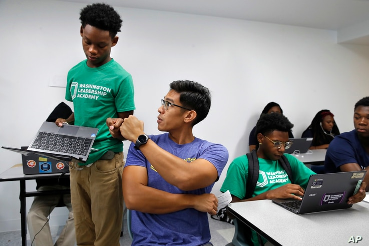 """Tamar Champion, 14, left, gets a """"fist bump"""" from teacher Enrique Ramos, as he shows his teacher his results after taking a diagnostic test using special software in his literacy studio class at the Washington Leadership Academy, Aug. 23, 2017, in Wa..."""