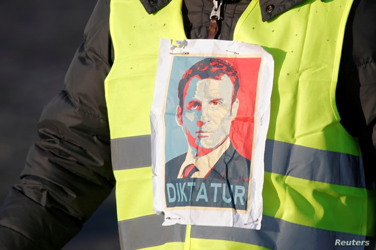 "A ""Yellow Vest"" protester sports an image of French President Emmanuel Macron, with ""Diktatur,"" the German word for ""Dictatorship,"" written on it, in Paris, France, Nov. 17, 2018."